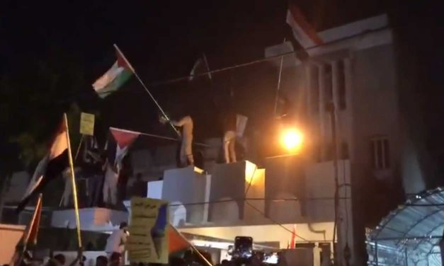 Iraqis storm Bahrain embassy in Baghdad; wave Palestinian flags from roof of building