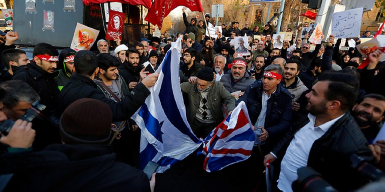 Iranian militia surround UK embassy in Tehran, burn British and Israel flags, amid escalating tensions between Britain and Iran